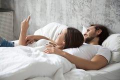 Ευτυχές χιλιετές ζεύγος που χρησιμοποιεί το κινητό τηλέφωνο που βρίσκεται στο κρεβάτι από κοινού Στοκ Εικόνες
