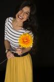 Ευτυχές όμορφο θηλυκό πρότυπο που κρατά ένα μεγάλο κίτρινο χαμόγελο λουλουδιών Στοκ εικόνα με δικαίωμα ελεύθερης χρήσης