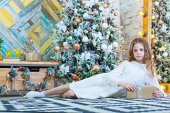 Ευτυχές όμορφο κορίτσι παιδιών με το χριστουγεννιάτικο δώρο στο σπίτι στο πάτωμα Στοκ Φωτογραφία