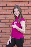 Ευτυχές όμορφο κορίτσι που παρουσιάζει αντίχειρα επάνω στο σύμβολο Στοκ φωτογραφία με δικαίωμα ελεύθερης χρήσης