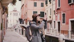 Ευτυχές όμορφο κορίτσι τουριστών που παίρνει τις φωτογραφίες smartphone που περπατούν στην καταπληκτική οδό καναλιών νερού στη Βε απόθεμα βίντεο