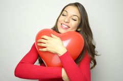 Ευτυχές όμορφο κοριτσιών μπαλόνι αέρα καρδιών αγκαλιάσματος κόκκινο στο γκρίζο υπόβαθρο Έννοια ημέρας βαλεντίνων ` s Στοκ Φωτογραφίες