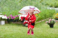 Ευτυχές όμορφο μικρό κορίτσι διασκέδασης στο κόκκινο αδιάβροχο με την ομπρέλα που περπατά το καλοκαίρι πάρκων Στοκ Εικόνες
