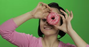 Ευτυχές όμορφο νέο κορίτσι που θέτει και που έχει τη διασκέδαση με doughnut E απόθεμα βίντεο