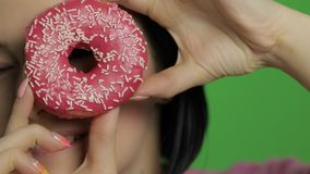 Ευτυχές όμορφο νέο κορίτσι που θέτει και που έχει τη διασκέδαση με doughnut E φιλμ μικρού μήκους
