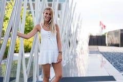 Ευτυχές όμορφο ξανθό χαμόγελο γυναικών που εξετάζει τη κάμερα και το π Στοκ Εικόνες