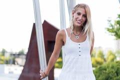 Ευτυχές όμορφο ξανθό χαμόγελο γυναικών που εξετάζει τη κάμερα και το π Στοκ Φωτογραφία