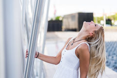 Ευτυχές όμορφο ξανθό χαμόγελο γυναικών που εξετάζει τη κάμερα και το π Στοκ Φωτογραφίες