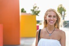Ευτυχές όμορφο ξανθό χαμόγελο γυναικών που εξετάζει τη κάμερα και το π Στοκ Εικόνα