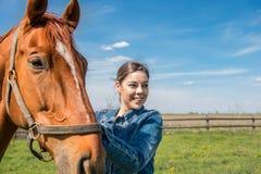 Ευτυχές όμορφο brunette που φροντίζει το καφετί άλογό της Στοκ εικόνες με δικαίωμα ελεύθερης χρήσης