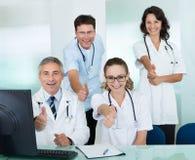 Ευτυχές δόσιμο ιατρικών ομάδων αντίχειρες επάνω Στοκ Εικόνες