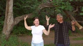 Ευτυχές ώριμο ζεύγος που έχει τη διασκέδαση στο πάρκο φιλμ μικρού μήκους