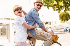 Ευτυχές ώριμο ζεύγος που πηγαίνει για έναν γύρο ποδηλάτων στην πόλη Στοκ Εικόνες