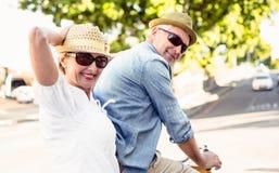 Ευτυχές ώριμο ζεύγος που πηγαίνει για έναν γύρο ποδηλάτων στην πόλη Στοκ Εικόνα