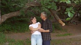 Ευτυχές ώριμο ζεύγος που χορεύει στο πάρκο, σε αργή κίνηση φιλμ μικρού μήκους