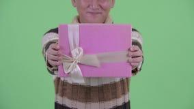 Ευτυχές ώριμο ιαπωνικό άτομο που δίνει το κιβώτιο δώρων φιλμ μικρού μήκους