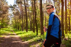 Ευτυχές bicyclist νεαρών άνδρων που οδηγά ένα δασικό άτομο οδικών ποδηλάτων την άνοιξη που παρουσιάζει χέρι με τον αντίχειρα επάν Στοκ φωτογραφία με δικαίωμα ελεύθερης χρήσης