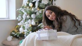 Ευτυχές brunette με το δώρο που χαμογελά και που εξετάζει τη κάμερα που βρίσκεται στον καναπέ στο πράσινο δέντρο υποβάθρου με τα  φιλμ μικρού μήκους