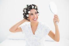 Ευτυχές brunette στους κυλίνδρους τρίχας που φαίνονται διαθέσιμος καθρέφτης χεριών Στοκ Φωτογραφίες