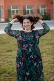 Ευτυχές curvy κορίτσι με τη σγουρή τρίχα στην οδό σχετικά με την τρίχα της Στοκ Φωτογραφίες