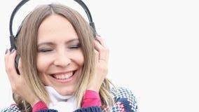 Ευτυχές flirty κορίτσι με τα ακουστικά που ακούει τη μουσική, κλείσιμο του ματιού φιλιών φυσήγματος φιλμ μικρού μήκους