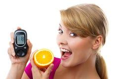 Ευτυχές glucometer εκμετάλλευσης γυναικών και κατανάλωση του φρέσκου πορτοκαλιού, μετρώντας και ελέγχοντας το επίπεδο ζάχαρης, έν στοκ εικόνες με δικαίωμα ελεύθερης χρήσης