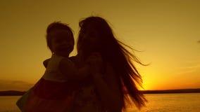 Ευτυχές mom που χορεύει με την λίγη κόρη στο ηλιοβασίλεμα στο υπόβαθρο μιας όμορφης λίμνης απόθεμα βίντεο