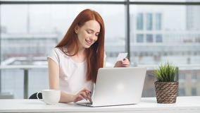 Ευτυχές redhead κορίτσι που ψωνίζει on-line με την πιστωτική κάρτα και το lap-top απόθεμα βίντεο