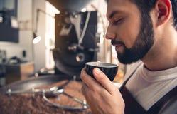 Ευτυχές roaster καφέ που δοκιμάζει το καυτό υγρό Στοκ φωτογραφία με δικαίωμα ελεύθερης χρήσης