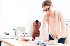 Ευτυχές seamstress γυναικών που φορά τα γυαλιά που στέκονται και που σύρουν στο εργαστήριο Στοκ Εικόνες