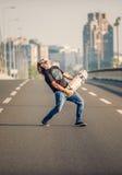 Ευτυχές skateboarder στην κιθάρα παιχνιδιού γεφυρών boa σαλαχιών του Στοκ εικόνες με δικαίωμα ελεύθερης χρήσης