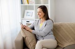 Ευτυχές texting μήνυμα γυναικών στο smartphone στο σπίτι στοκ φωτογραφία