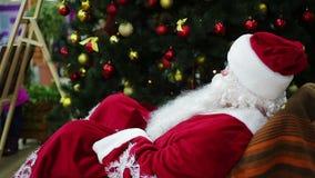 Ευτυχής Άγιος Βασίλης που κυματίζει παραδίδει rocker την καρέκλα για να καλωσορίσει τους ψωνίζοντας επισκέπτες λεωφόρων απόθεμα βίντεο