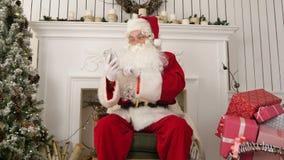 Ευτυχής Άγιος Βασίλης που ελέγχει επάνω τα ηλεκτρονικά ταχυδρομεία Χριστουγέννων από τα παιδιά στο τηλέφωνό του φιλμ μικρού μήκους