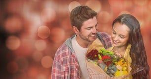 Ευτυχής άνδρας που εξετάζει τη γυναίκα με τα λουλούδια πέρα από το bokeh Στοκ Φωτογραφία