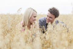 Ευτυχής άνδρας που εξετάζει τη γυναίκα χαλαρώνοντας στη μέση του τομέα Στοκ Φωτογραφία