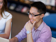 Ευτυχής άνδρας σπουδαστής που εργάζεται στη βιβλιοθήκη Στοκ εικόνα με δικαίωμα ελεύθερης χρήσης