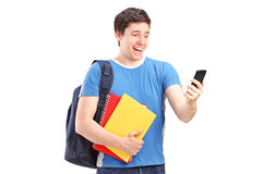 Ευτυχής άνδρας σπουδαστής που κοιτάζει στο τηλέφωνο κυττάρων του στοκ φωτογραφίες με δικαίωμα ελεύθερης χρήσης