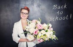 Ευτυχής δάσκαλος με τα λουλούδια στο υπόβαθρο πινάκων Στοκ εικόνες με δικαίωμα ελεύθερης χρήσης