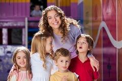 Ευτυχής δάσκαλος με τα χαριτωμένα παιδιά στον παιδικό σταθμό στοκ εικόνες