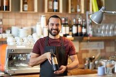 Ευτυχής άτομο ή σερβιτόρος με το μπουκάλι του κόκκινου κρασιού στο φραγμό Στοκ φωτογραφία με δικαίωμα ελεύθερης χρήσης