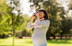 Ευτυχής έγκυος ασιατική γυναίκα με τη κάμερα στο πάρκο Στοκ εικόνα με δικαίωμα ελεύθερης χρήσης