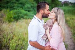 Ευτυχής έγκυος γυναίκα και ο σύζυγός της στο πάρκο Στοκ εικόνα με δικαίωμα ελεύθερης χρήσης