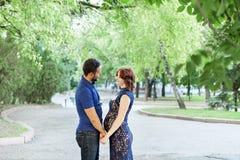 Ευτυχής έγκυος γυναίκα με τη στάση συζύγων μαζί στο φύλλωμα Στοκ φωτογραφία με δικαίωμα ελεύθερης χρήσης