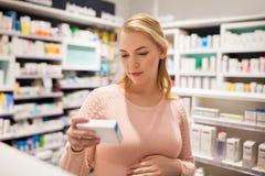 Ευτυχής έγκυος γυναίκα με το φάρμακο στο φαρμακείο Στοκ Εικόνες