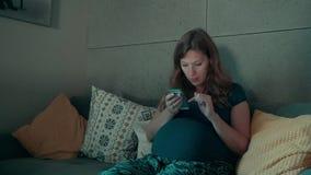 Ευτυχής έγκυος γυναίκα με το smartphone στο σπίτι φιλμ μικρού μήκους