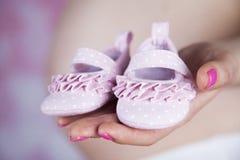 Ευτυχής έγκυος γυναίκα, παπούτσια μωρών στα χέρια της στοκ εικόνες