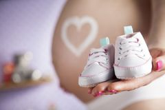 Ευτυχής έγκυος γυναίκα, παπούτσια μωρών στα χέρια της στοκ εικόνες με δικαίωμα ελεύθερης χρήσης