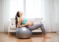 Ευτυχής έγκυος γυναίκα που ασκεί στο fitball στο σπίτι Στοκ Εικόνα