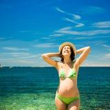 Ευτυχής έγκυος γυναίκα που κάνει ηλιοθεραπεία στη θάλασσα Στοκ Φωτογραφίες